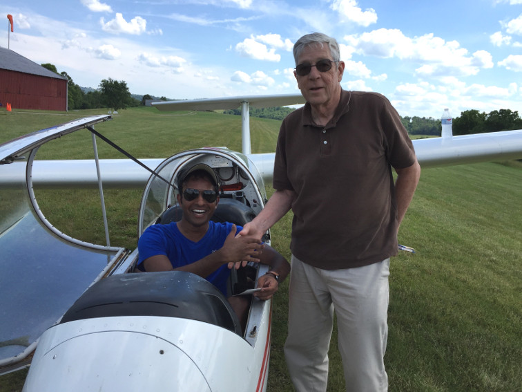 """Dan Pothala joined us in early June with a Single Engine Land rating, and very quickly adapted to flight without an engine. His first solo glider flight in our Blanik L23 was on June 18, 2016. His nearly 40 minute flight earned him his SSA """"A"""" badge. The very next day his 0.9 hr solo was commemorated by a """"B"""" badge. He is shown while still in the cockpit being congratulated by Al Bennett, CFIG."""