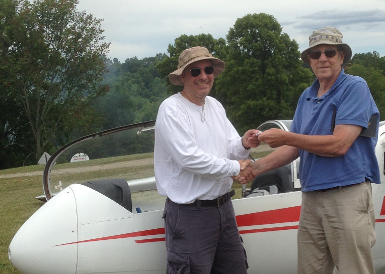 """Pittsburgh, PA, July 2, 2016: On this fine day, another of our new 2016 members has soloed the PSA Super Blanik L23. Maurio Mastroberardino joined us in late April with extensive power experience – including SEL high performance, complex and tailwheel endorsements. His only challenge was the FAA requirement for a current flight review. Maurio is a welcome addition to our Roster. He is eagerly working toward soloing our single place ships – and joining our tow team. Maurio is shown receiving his """"A"""" badge and congratulations from Al Bennett CFIG."""
